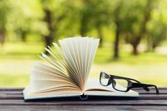 在公园打开书和镜片在一条长凳在一个晴天,读在夏天,教育,课本,回到学校概念 免版税库存照片