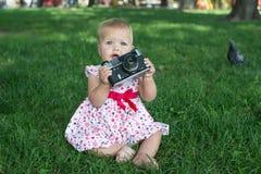 在公园拍与一台照片照相机的照片的女孩 库存图片