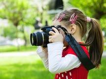 在公园拍与一台照片照相机的照片的女孩 免版税图库摄影