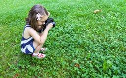 在公园拍与一台照片照相机的照片的女孩 免版税库存图片