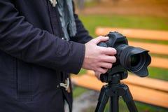 在公园拍摄某事在三脚架的一台照相机的欧洲人的手 免版税库存照片