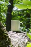 在公园树的一个独奏空白的加奶咖啡杯子 图库摄影