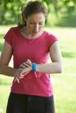 在公园检查时间的女性赛跑者使用秒表 免版税库存图片