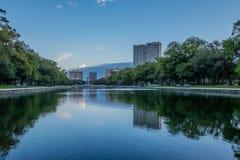 在公园水池的城市反射 免版税库存图片