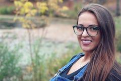 在公园水湖玻璃的少妇佩带的牛仔裤变褐室外头发的画象 免版税图库摄影