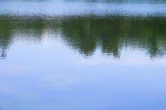在公园浇灌与阴影树和天空的反射 免版税库存照片