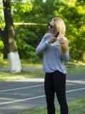 在公园炫耀妇女行使户外健身跟踪仪便携的技术的 免版税库存照片