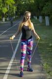 在公园炫耀妇女行使户外健身跟踪仪便携的技术的 库存照片