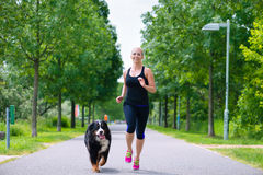 在公园炫耀室外-跑与狗的少妇 免版税库存照片