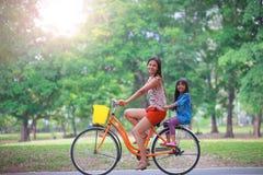 在公园照顾和女儿循环的自行车 免版税库存图片