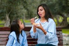 在公园照顾和她的小女儿坐一条长凳 免版税库存照片