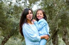 在公园照顾运载她逗人喜爱和微笑的女儿 图库摄影