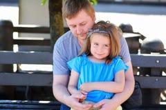 在公园生拥抱长凳的女儿在晴朗的夏日 免版税库存图片