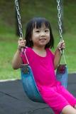 在公园的亚洲孩子摇摆 库存照片