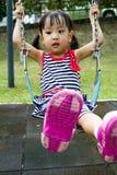 在公园的亚洲孩子摇摆 图库摄影