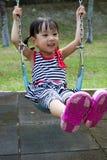 在公园的亚洲孩子摇摆 库存图片