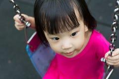 在公园的亚洲孩子摇摆 免版税库存照片