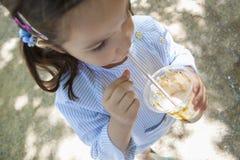 在公园的小女孩饮用的奶昔 图库摄影