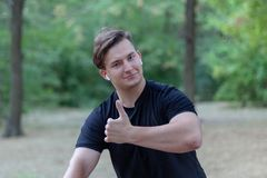 在公园的年轻英俊的白种人人赞许 库存图片