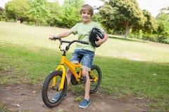 在公园的微笑的男孩骑马自行车 免版税库存照片