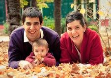 在公园的愉快的家庭在秋天 图库摄影