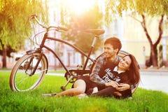 在公园的愉快的微笑的年轻夫妇在葡萄酒附近骑自行车 免版税库存照片