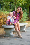 在公园的愉快的母亲和女儿谈的手机 库存图片