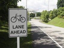 在公园的白色自行车道标志 免版税库存图片