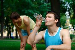 年轻在公园的运动员饮用水 库存图片