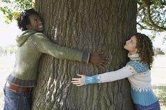 在公园的年轻夫妇拥抱树干 库存照片