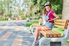 在公园的年轻美丽的妇女阅读书 图库摄影