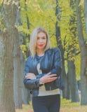 在公园秋天天步行一个可爱的女孩 免版税图库摄影