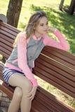 在公园称呼女孩坐一条长凳 库存照片