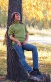 在公园结构树附近的秋天女孩 库存照片