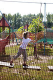 在公园绳索的乐趣-女孩克服阻碍 免版税库存图片