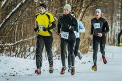 在公园编组年轻跑通过多雪的足迹的人和女孩 免版税图库摄影
