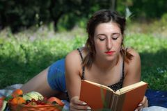 在公园草的女孩,读一本书并且吃果子 库存照片