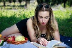 在公园草的女孩,读一本书并且吃果子 免版税库存图片