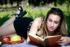 在公园草的女孩,读一本书并且吃果子 库存图片