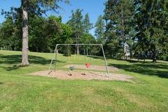在公园设置设置的空的小孩摇摆 免版税库存照片