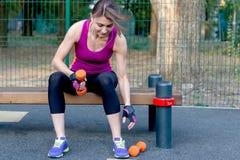 在公园运动场的年轻白种人妇女锻炼,举行哑铃,坐娱乐酒吧;黑和淡紫色运动服 免版税库存图片