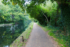 在公园远足足迹的步行道路在水道在Woking 库存图片