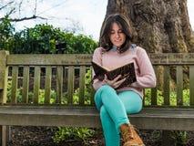 在公园长椅的俏丽的妇女阅读书 免版税库存图片