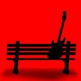 在公园长椅的吉他 免版税库存照片