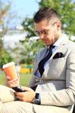 在公园长椅的商人使用手机 免版税图库摄影