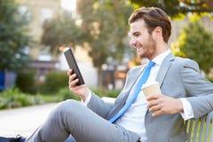在公园长椅的商人用使用数字式片剂的咖啡 图库摄影