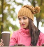 在公园长椅的妇女饮用的咖啡在秋叶下 免版税库存照片