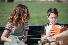 在公园长椅的安静的读书 免版税库存图片