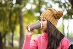 在公园长椅的秋天妇女饮用的咖啡在秋叶下 免版税库存图片