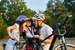在公园骑马自行车的家庭 两个女孩乘驾骑自行车与他们的父亲 免版税库存图片